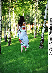 young woman - beautiful woman walking on grass in birch...
