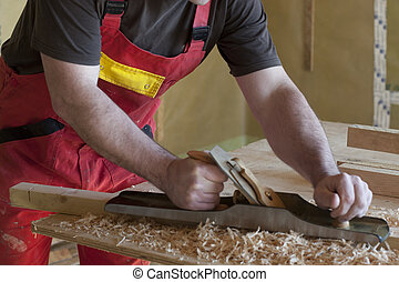 carpenter works on a wood house with a planer