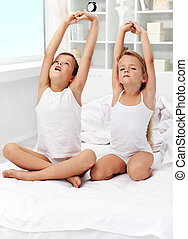 Kids waking up and stretching their arms on the bed