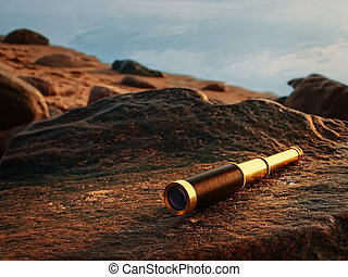 antique brass telescope at sea coast stone