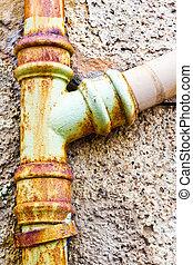 Drainpipe - A rusty drainpipe against a stone wall