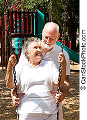 Senior Couple at Play - Senior couple on a playground,...