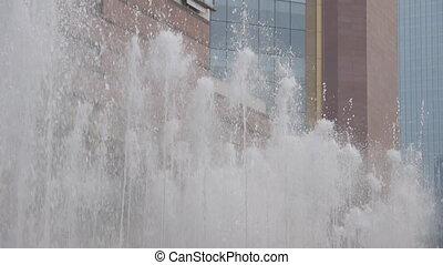 Urban fountain before modern building