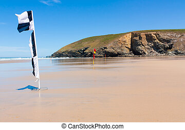 Lifeguard flags on the beach at Mawgan Porth near Newquay...