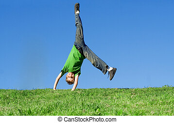 happy kid doing cartwheel in summer