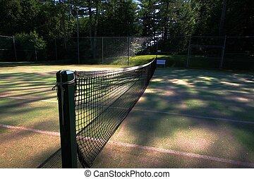 Zen tennis net - View of a tennis net on grass court as sun...