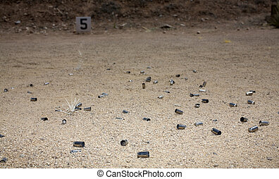Shooting practice - Lots of empty brass lying around a sandy...