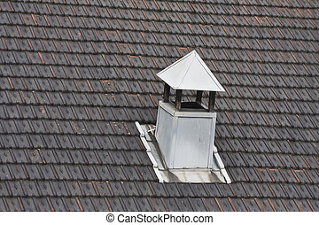 metal chimney on black tiled roof
