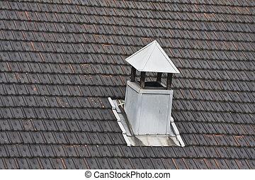 metal chimney on black tiled roof