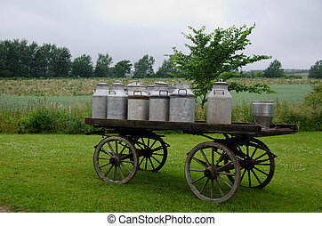Old milk cans on waggon - old traditional milk cans on a...