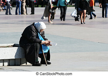 Homeless poor old woman - Poor old woman begging an alms on...