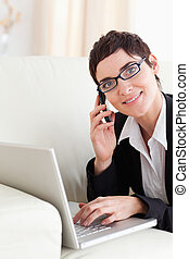 Businesswoman lying on a sofa with a laptop and a phone...