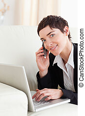 Cute Businesswoman lying on a sofa with a laptop and a phone...