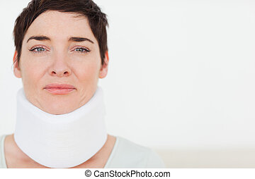 Close up of a sad Woman with a surgical collar in a waiting...