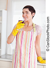 Woman in cleaning gown with a glass
