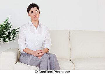 Beautiful brunette woman sitting on a sofa