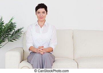 Brunette woman sitting on a sofa in a waiting room