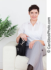 Short-haired businesswoman sitting on a sofa in a waiting...