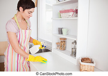 Beautiful brunette woman cleaning a cupboard in the kitchen
