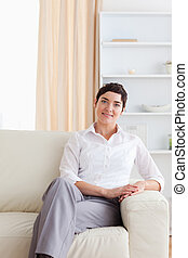 Charming woman sitting on a sofa in the living room