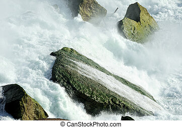 Rocks and Foam - Cascading water falling on hard rocks and...