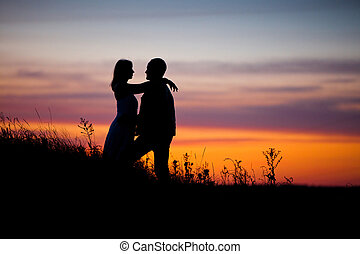 Couple on the sunset background. - Pretty couple in the...