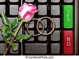 Wedding rings and red roses on computer keyboard. answer...