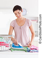 Charming Woman ironing clothes in a utility room