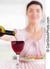 Brunette Woman pouring red wine in a glass in a kitchen
