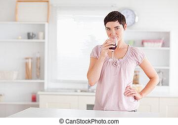 Joyful woman drinking wine in a kitchen