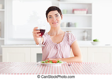 Cute Woman toasting with wine in a kitchen