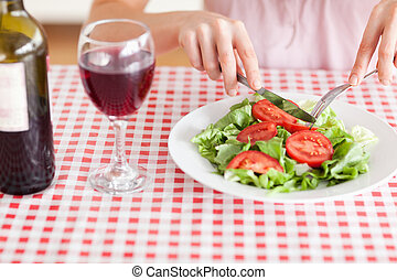 Charming Woman eating lunch and drinking wine in a kitchen
