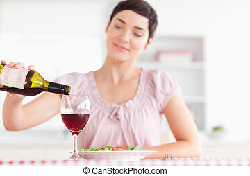 Charming Woman pouring redwine in a glass in a kitchen
