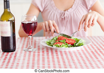 Cute Woman eating lunch and drinking wine in a kitchen