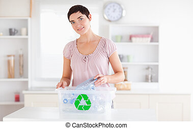 Smiling Woman putting bottles in a recycling box