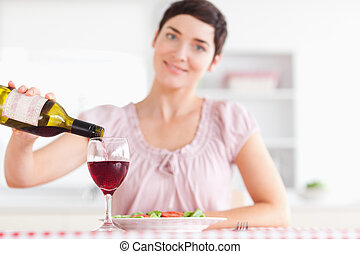 Smiling Woman pouring redwine in a glass in a kitchen