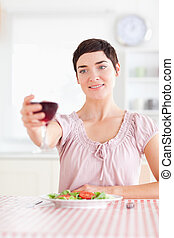Charming Woman toasting with wine in a kitchen
