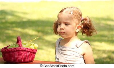 little girl eat grape