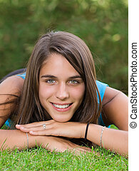 Cute young woman lying on grass in the park