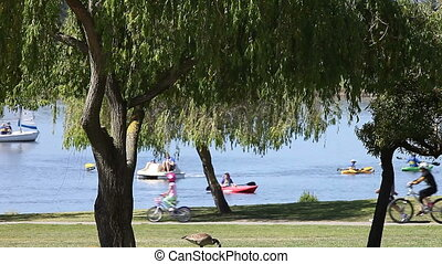 Sunday at the lake - boaters, bicyclists and walkers at a...