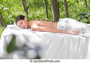 Young female receiving hot stone therapy - Beautiful young...