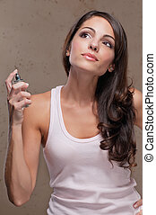 Woman spraying perfume - An attractive female spraying...