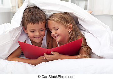 Enjoying the forbidden knowledge - kids reading in bed under...