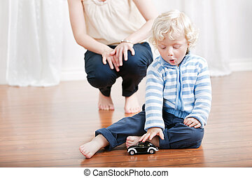 Cute boy playing with toy car