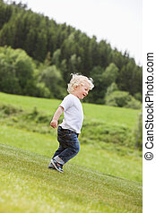 Toddler Boy Walking Alone in Garden
