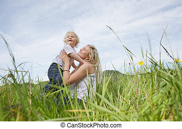 Mother sitting on grass while playing with boy - Low angle...