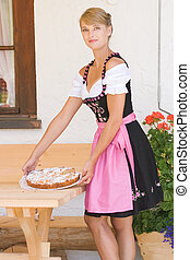 Young woman in dirndl with cake - Young Bavarian operation...