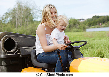 Mother and Child mowing grass - Smiling young woman with...