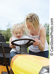 Young Boy with Mother on Garden Tractor - Young female with...