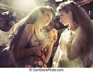 Two women holding magic flask